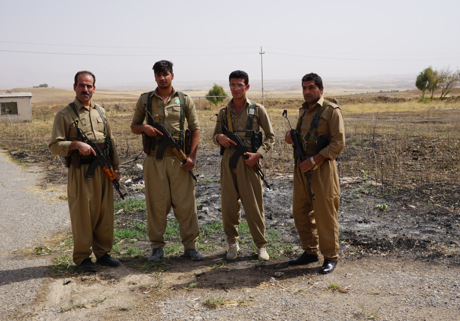 Peshmerga from the Democratic Party of Iranian Kurdistan stand for a photo at a secret location
