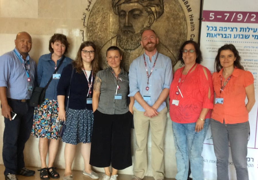 The group from Homerton Hospital stands in front of the plaque of Maimonides at Rambam Medical Cente
