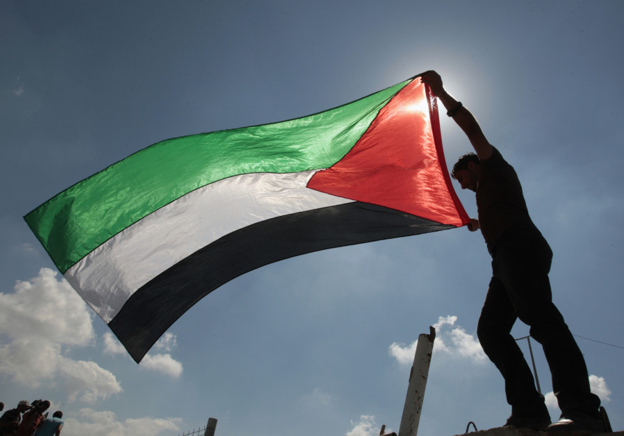 A Palestinian holds a flag during a protest