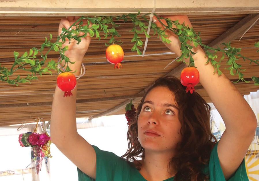 A girl decorates the sukka ahead of Succot.
