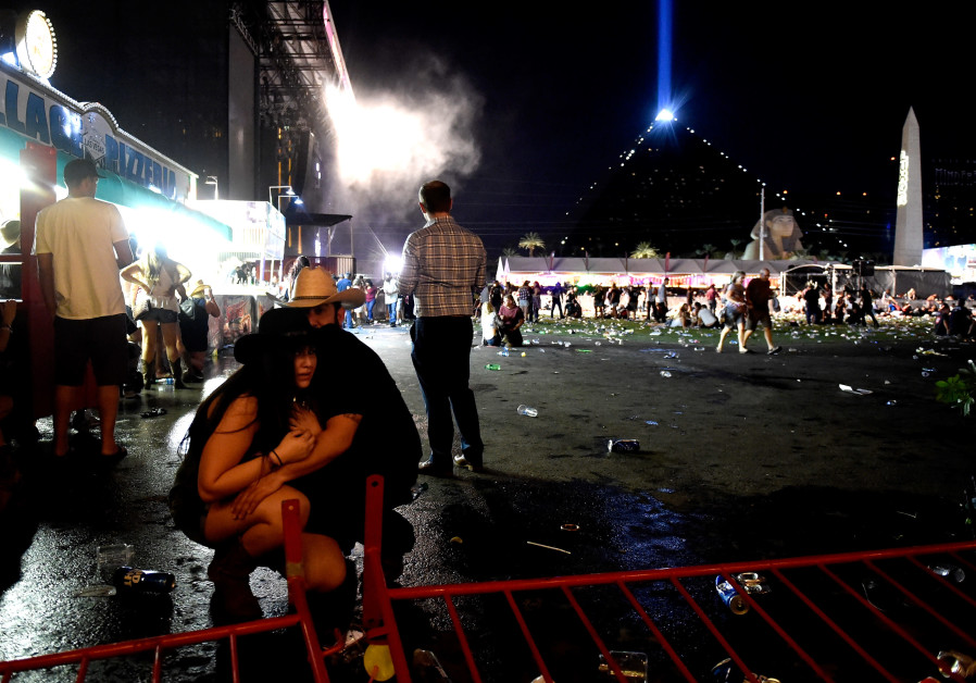 People take cover at the Route 91 Harvest country music festival in Las Vegas after gun fire