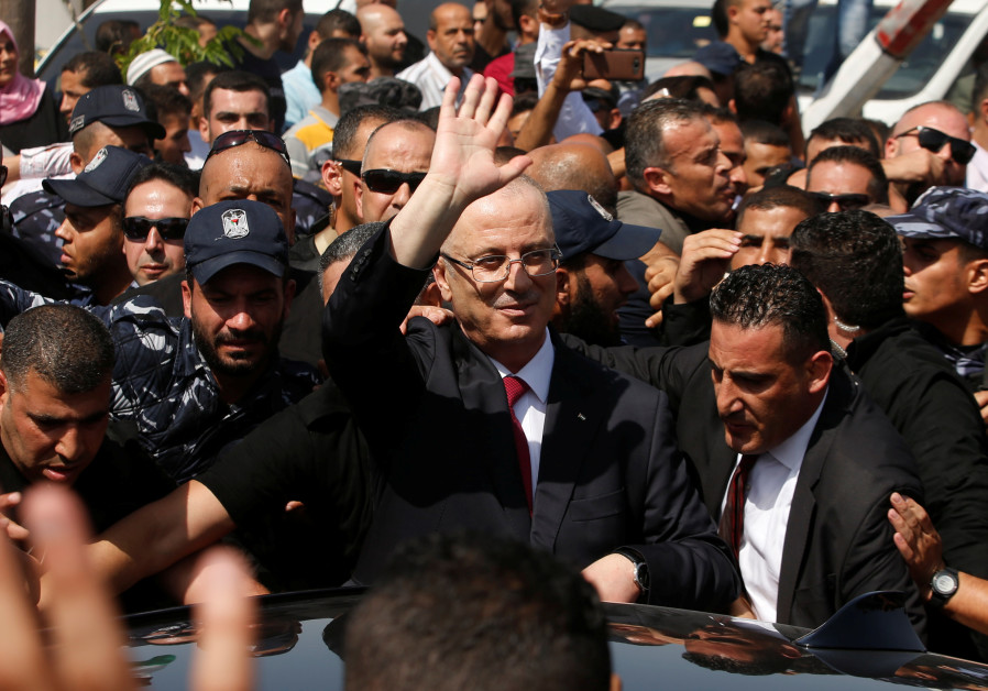 Palestinian Prime Minister Rami Hamdallah waves upon his arrival with his government ministers to ta