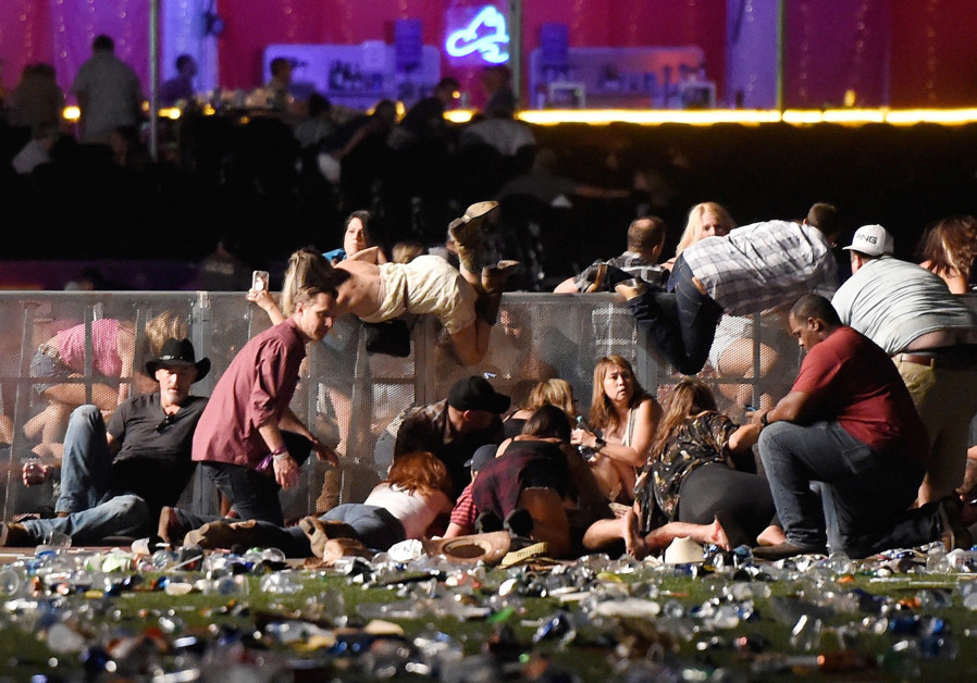 People scramble for shelter during a mass shooting at a music festival in Las Vegas