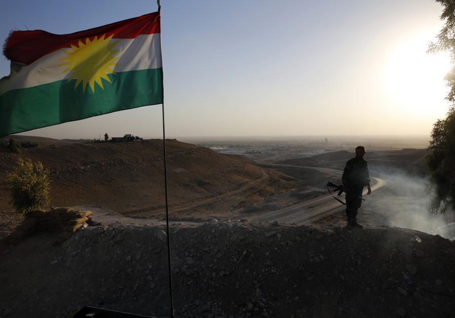 A Kurdish Peshmerga fighter looks down the road to Makhmur