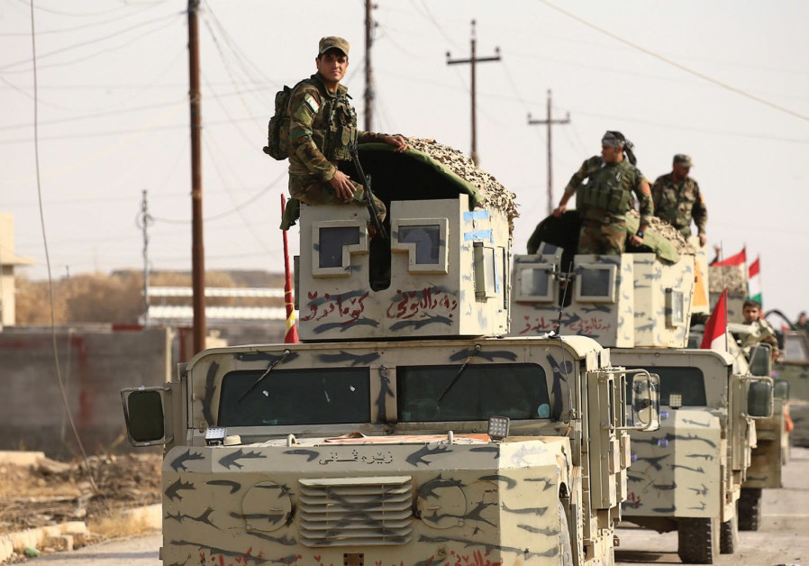 PESHMERGA FORCES ride on military vehicles in the town of Bashiqa