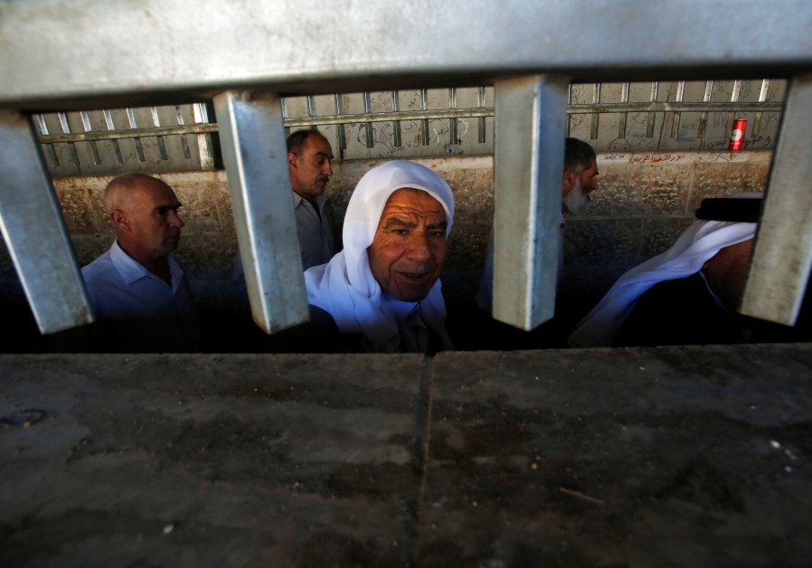 Palestinians cross an Israeli checkpoint in the West Bank city of Bethlehem