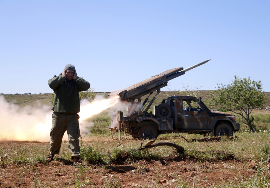 A Syrian rebel fires at forces loyal to Bashar Assad in Idlib, Syria