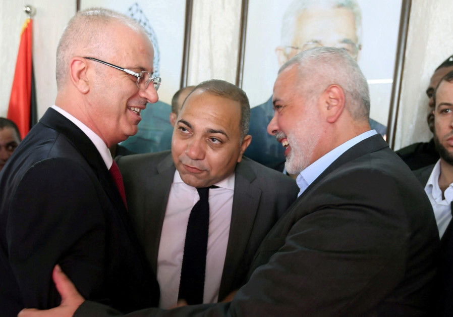 PALESTINIAN AUTHORITY Prime Minister Rami Hamdallah (left) shakes hands with Hamas chief Ismail Hani