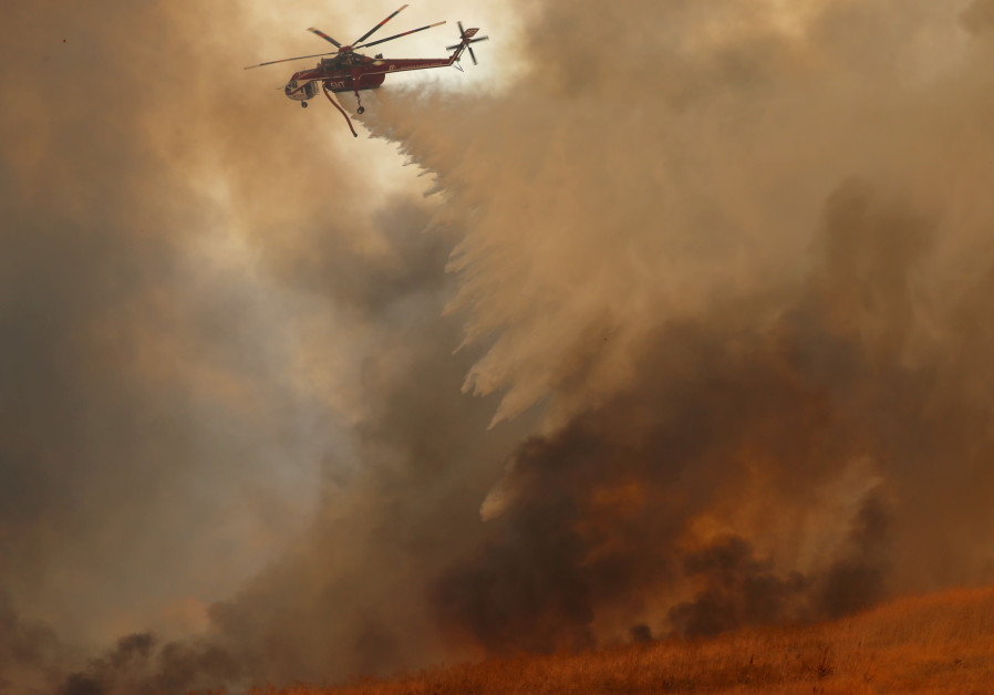 A helicopter drops water on a wind driven wildfire.