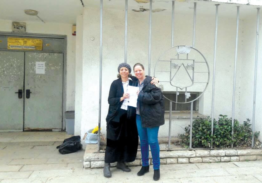 A FORMER 'chained' woman (left) stands in front of a rabbinic court with her lawyer after winning he