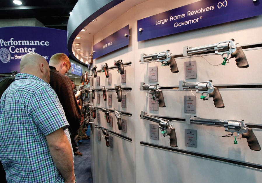 GUN ENTHUSIASTS look over Smith & Wesson guns at the National Rifle Association's annual meetings