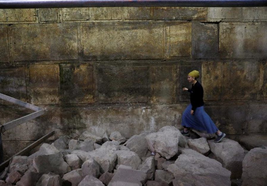 Israel Antiquities Authority archaeologist Tehillah Lieberman walks atop stones lying besides a part of the Western Wall, during a media tour revealing a theatre-like structure which was discovered during excavation works underneath Wilson's Arch in the Western Wall tunnels in Jerusalem's Old City,  (photo credit:REUTERS/Ronen Zvulun)