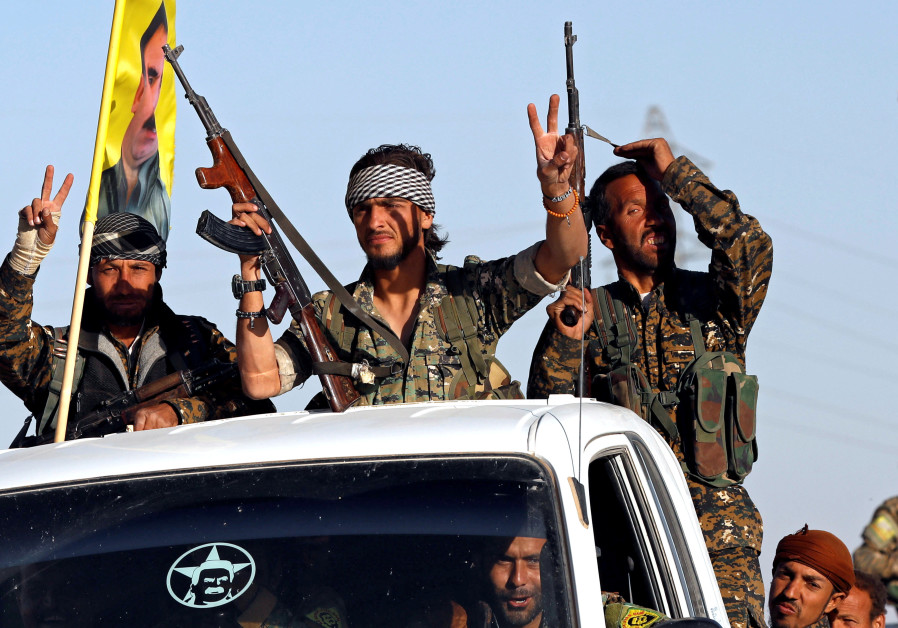 Fighters of Syrian Democratic Forces make the V-sign as their convoy passes in Ain Issa, Syria.