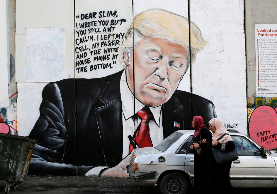 Palestinian women walk by a mural of Donald Trump on the West Bank separation wall, October 2017