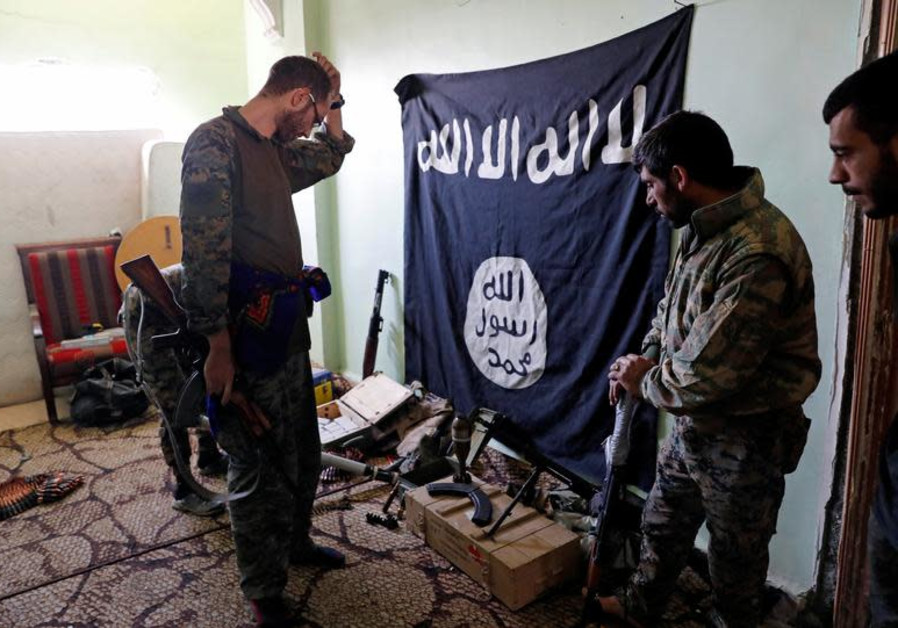 Fighters of Syrian Democratic Forces inspect weapons and munitions recovered at the former positions