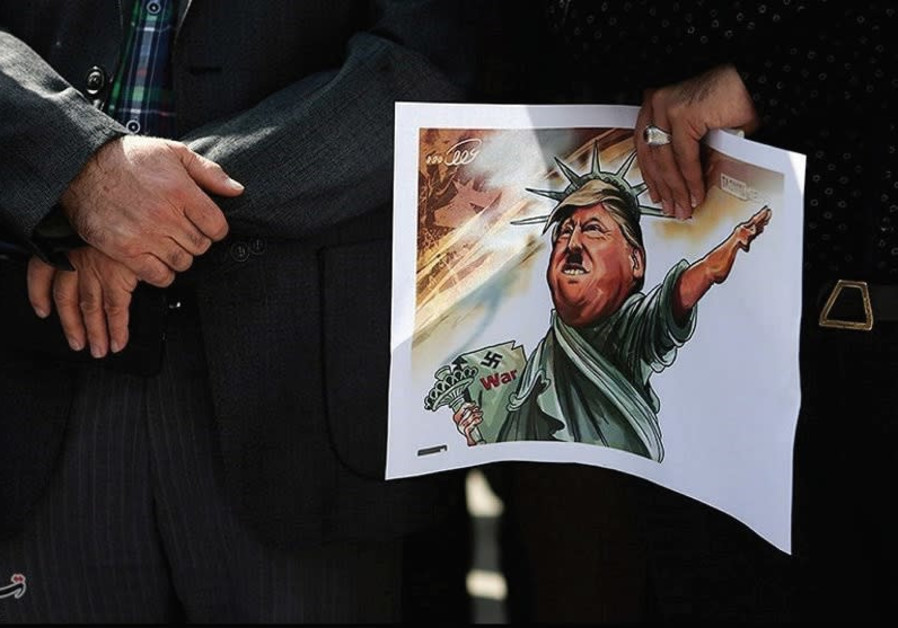 An Iranian student holds a caricature of US President Donald Trump during a protest against Trump's