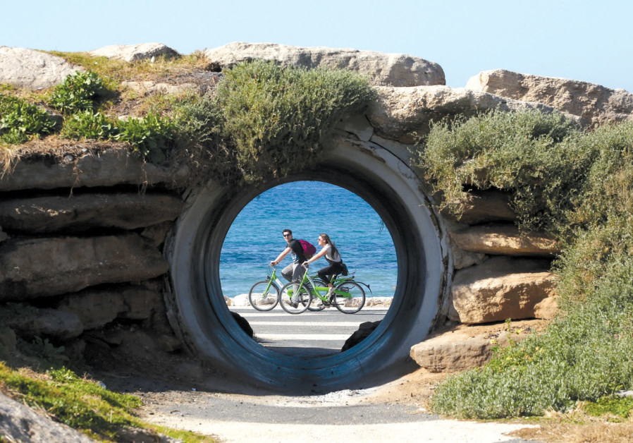 People enjoy a bike ride along Tel Aviv's promenade.