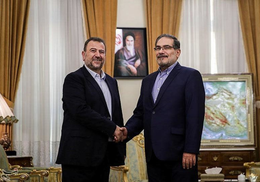 Saleh al-Arouri (L), Hamas deputy chief, shakes hands with Ali Shamkhani, secretary of Iran's Nation