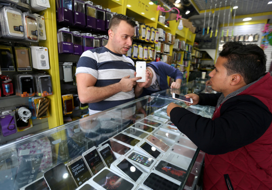 A Palestinian seller shows a smartphone to a customer in a mobile phone shop in Gaza City.