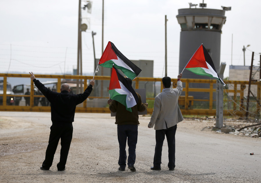 Palestinian protesters wave their national flag outside of an Israeli prison