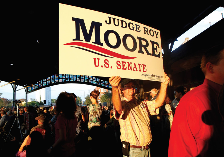 A supporter of US Senate candidate Judge Roy Moore holds a sign as he waits for a campaign rally in