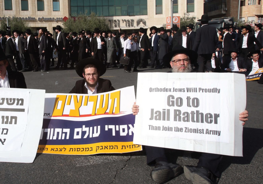 ULTRA-ORTHODOX protesters hold signs in Jerusalem during their 'day of rage,' declared to protest th