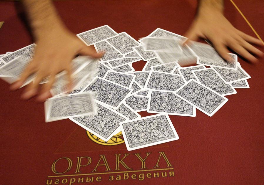 A dealer shuffles the cards.
