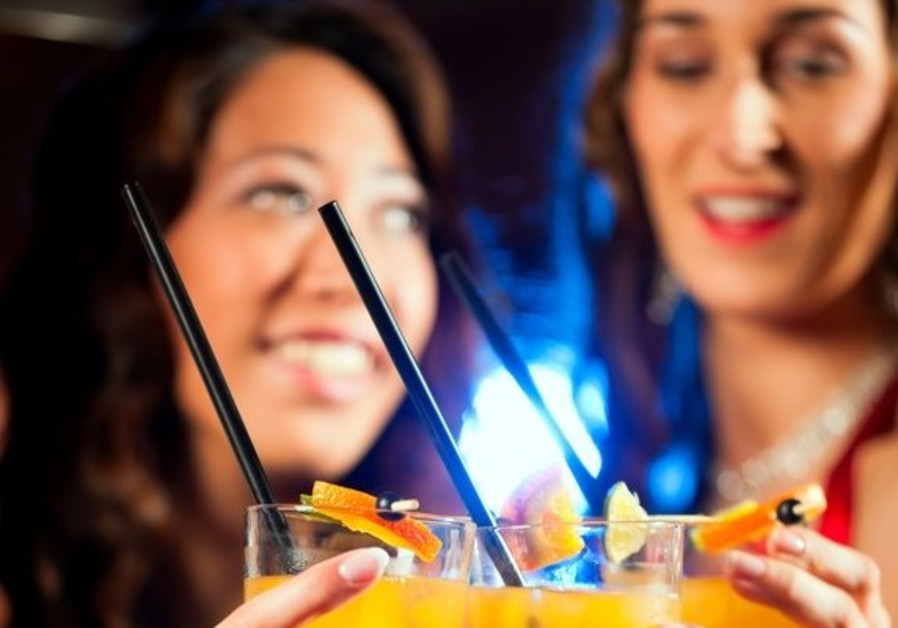 Women drink cocktails at a bar