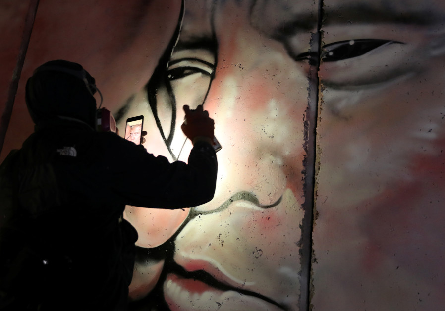 Lushsux works on mural (Credit: Ammar Awad/Reuters)
