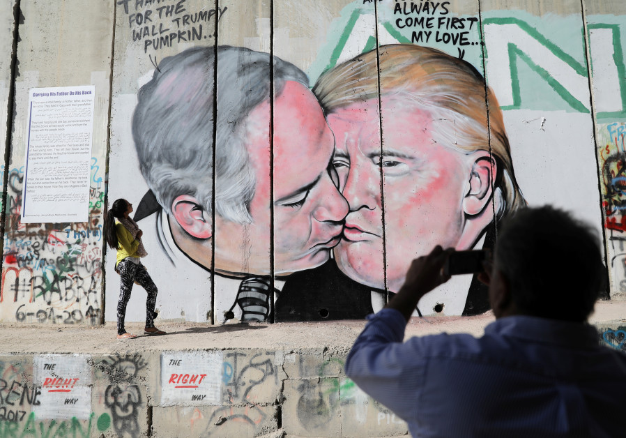 A man photographs a woman as she stands next to a mural depicting U.S. President Donald Trump and Is