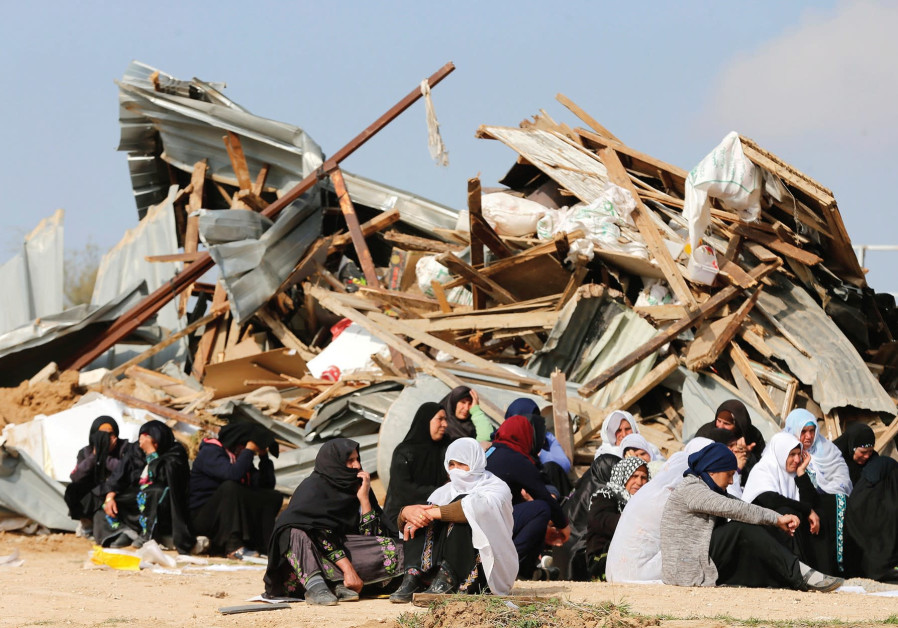 Beduin women sit beside ruins from of their homes in Umm el-Hiran, which was destroyed in January 20
