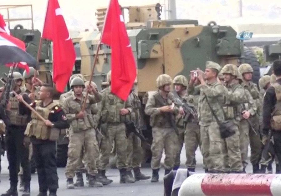 Iraqi and Turkish soldiers wave flags at the Habur Border Gate between Turkey and Iraq