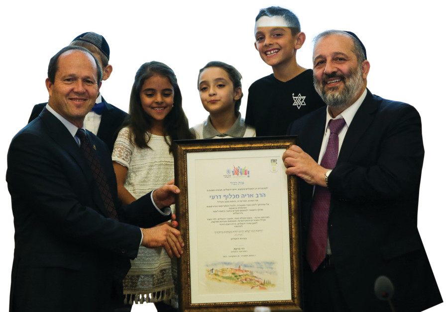 Mayor Nir Barkat (left) and Interior Minister Arye Deri (right) pose with local children at a festiv