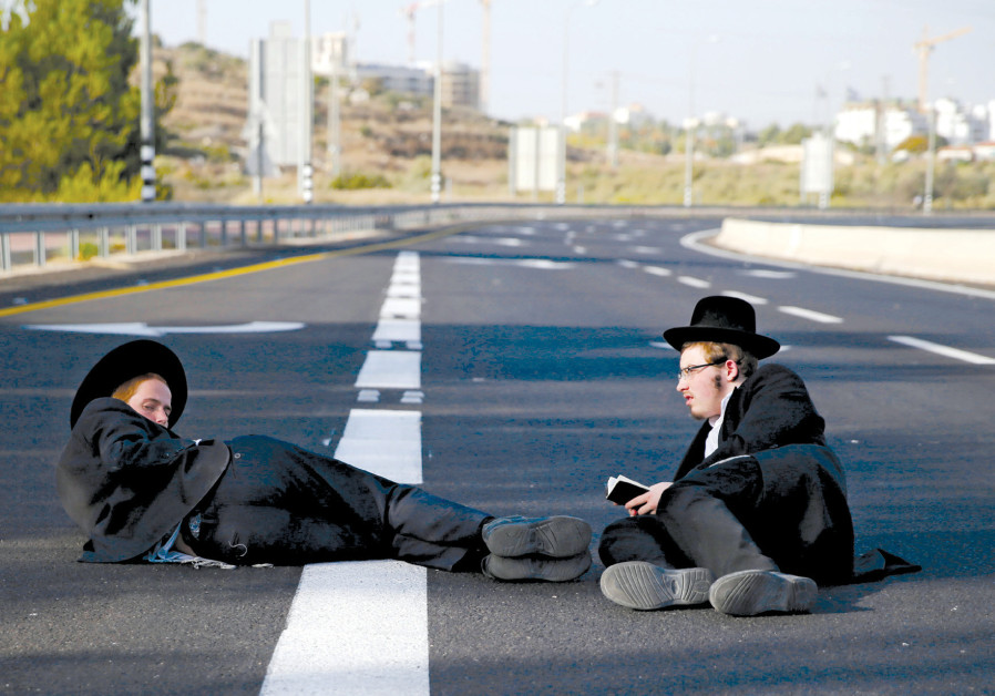 ULTRA-ORTHODOX men sit on a road during the 'day of rage' protest near Modi'in on October 19