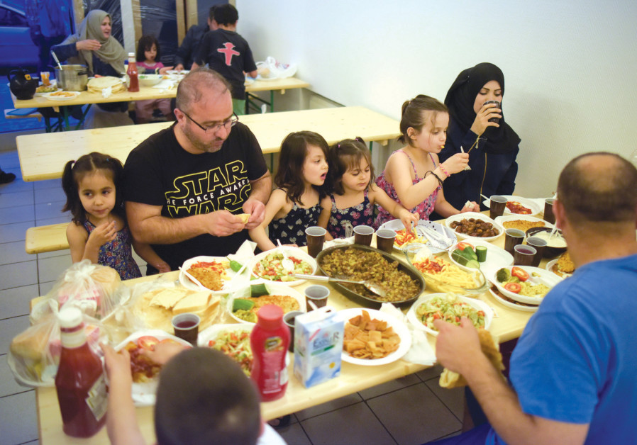 MEMBERS OF a Syrian family eat at a refugee shelter in a former hotel in Berlin in 2016