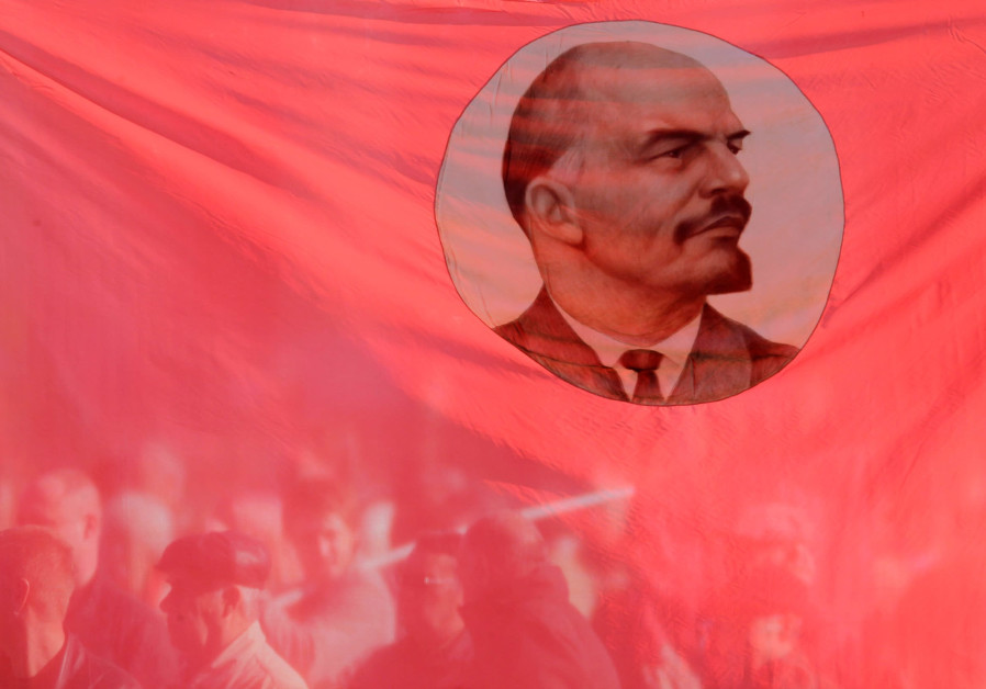 Russians hold up a flag emblazoned with Communist leader Vladimir Leninedu