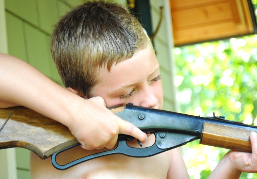 A young boy aiming a BB gun