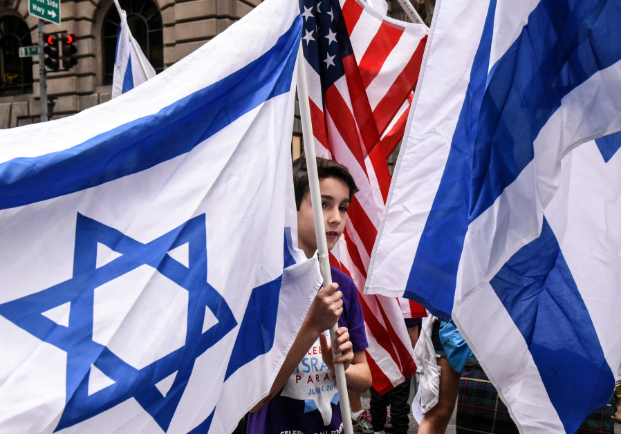 A boy is surrounded by Israeli and American flags
