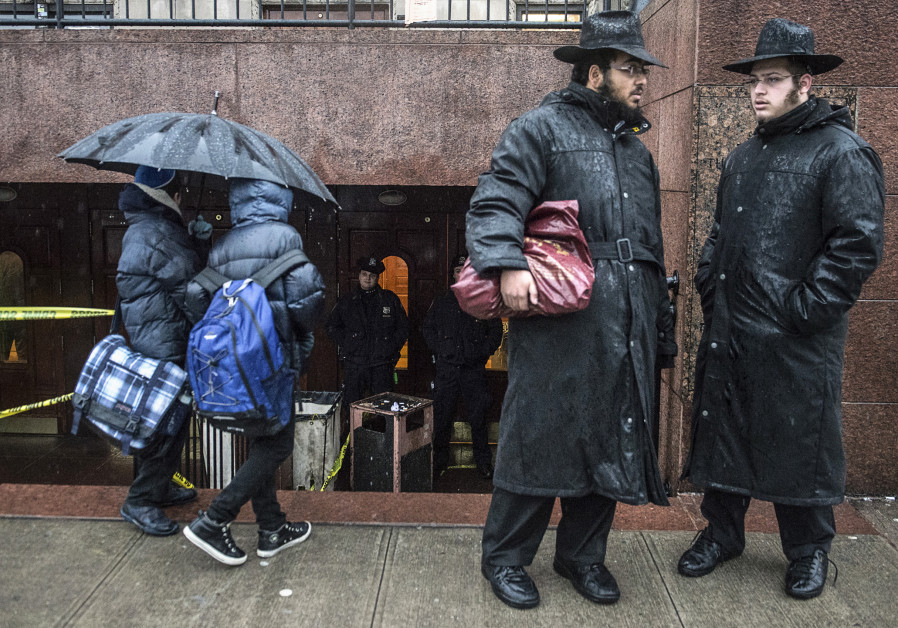 Policemen (background) keep guard as men and boys stand at a Brooklyn synagogue in New York City.