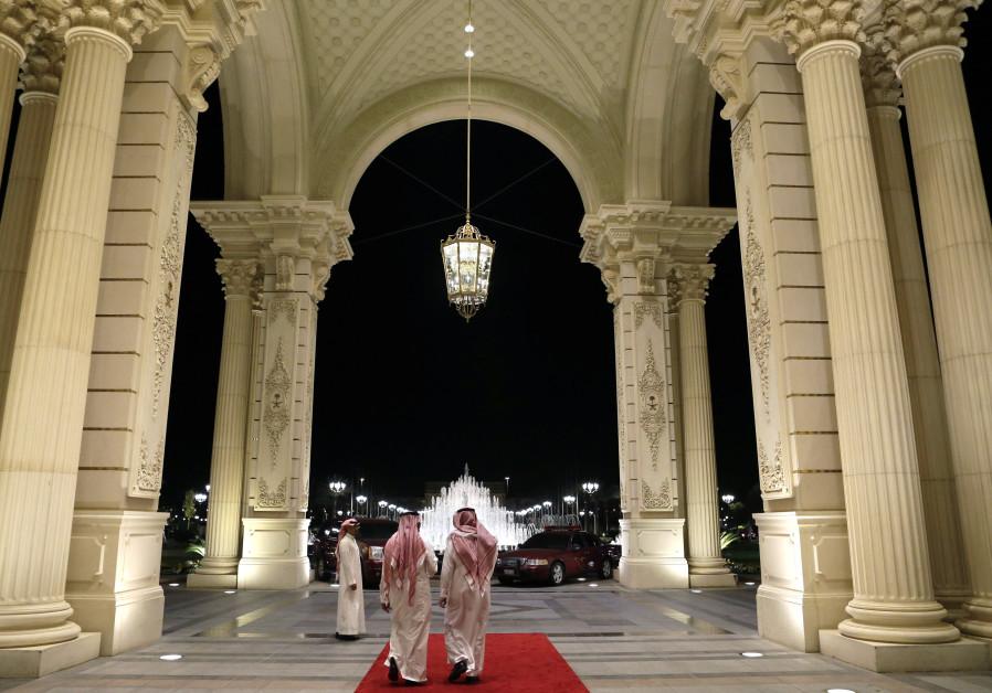 Saudi men walk at the entrance to the Ritz-Carlton Hotel.