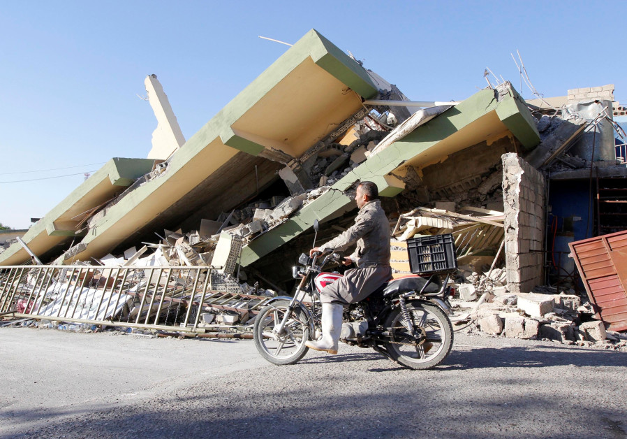 A man rides past the remains of a building in Darbandikhanm, Kurdistan, after a 7.2 magnitude earthq
