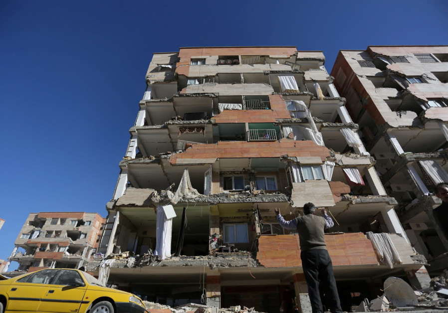A man reacts as he looks at a damaged building following an earthquake in Iran