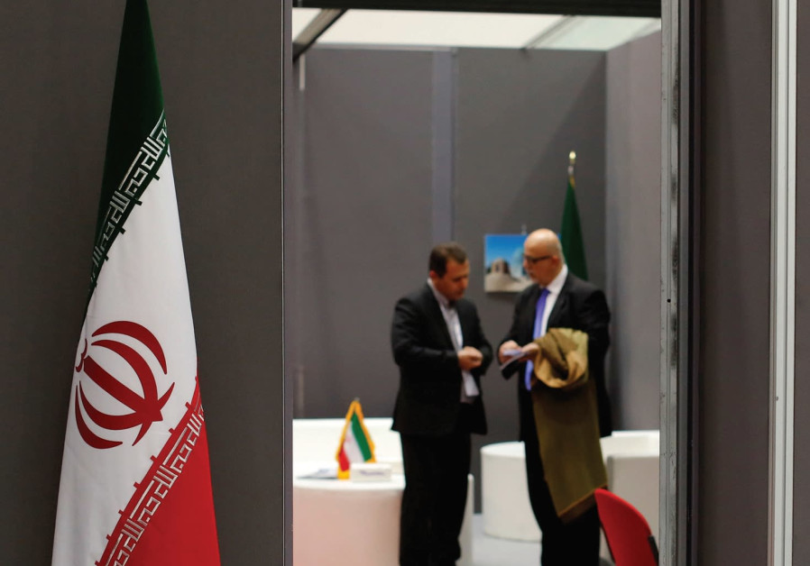 IRANIAN EXHIBITORS stand in a booth during the opening of the fair 'Iran country presentation' in Ro