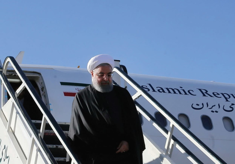 IRANIAN PRESIDENT Hassan Rouhani walks down aircraft steps as he arrives at Kermanshah near the area