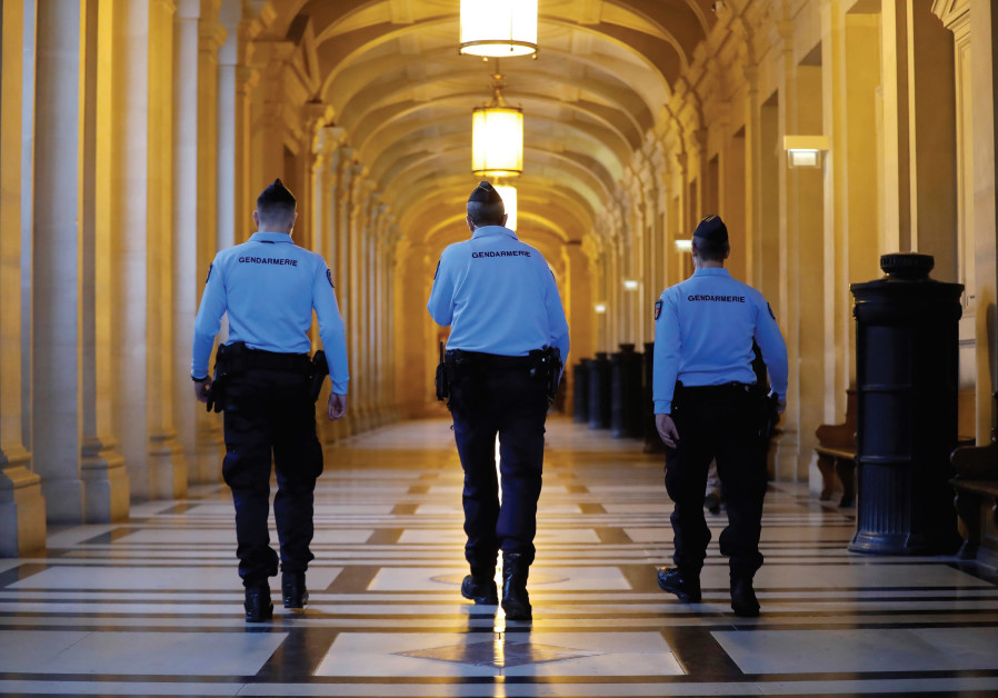FRENCH GENDARMES walk in the corridors of a Paris courthouse before the verdict in the trial of Abde
