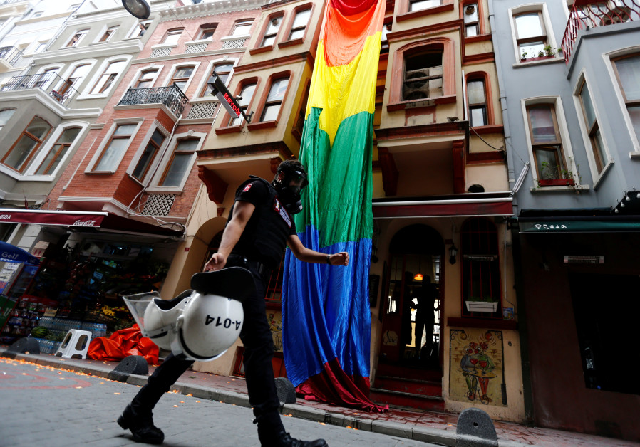 A riot police, with a rainbow flag in the background, chases LGBT rights activists in Turkey