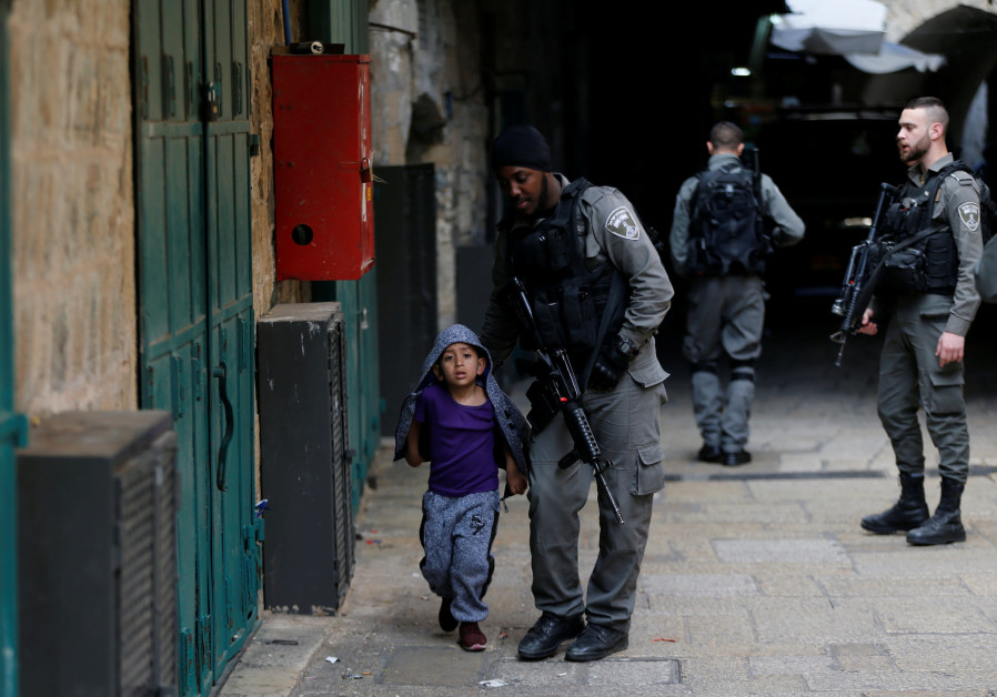 An Israeli border policeman escorts a boy away from a blocked alley in Jerusalem