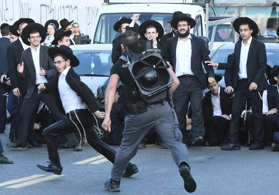 A policeman chases an Ultra-Orthodox protestor in Bnei Brak. (Photo: Avraham Sassoni/Maariv)