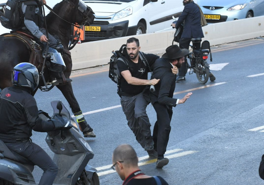 A policeman tackles an Ultra-Orthodox protestor in Bnei Brak. (Photo: Avraham Sassoni/Maariv)