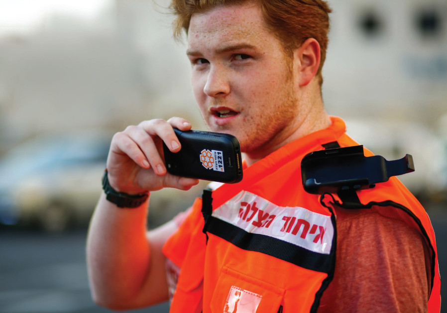 A UNITED HATZALAH volunteer holds the new smartphone mobile device that will be issued to all of the